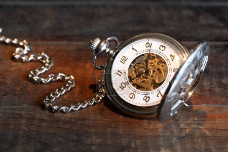 Photo for Vintage pocket watch with open lid and chain on wooden surface - Royalty Free Image