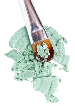Photo pour Pinceau de maquillage avec verte concassée ombre à paupières, isolé sur blanc macro - image libre de droit