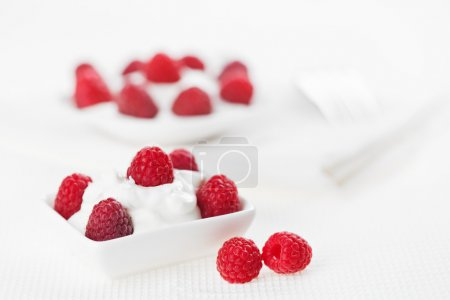 Still life with raspberry sour cream dessert on white linen tabl