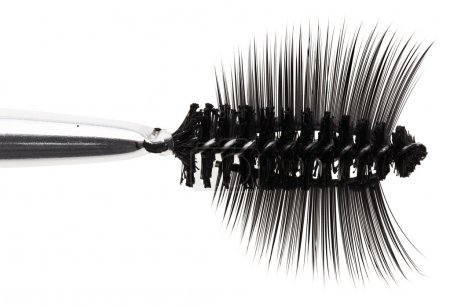 Black mascara brush and false eyelashes abstract composition, on