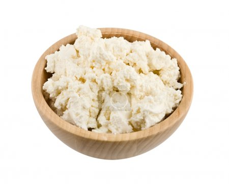 Fresh cottage cheese in wooden bowl