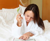 Mladá žena v posteli čtení knihy