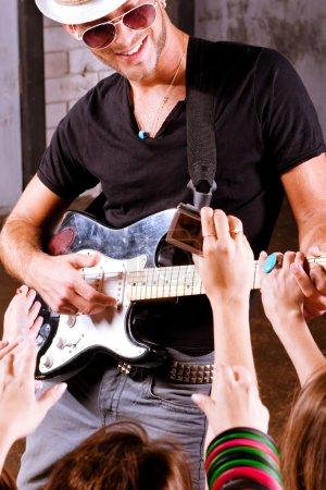 Photo pour Guitariste de rock jouer devant une foule enthousiaste. - image libre de droit