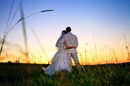 Photo pour Couple de mariage à la recherche dans la colline de montagne sur le coucher de soleil - image libre de droit