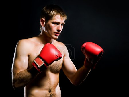 Photo pour Portrait de jeune homme avec des gants de boxe sur fond noir - image libre de droit
