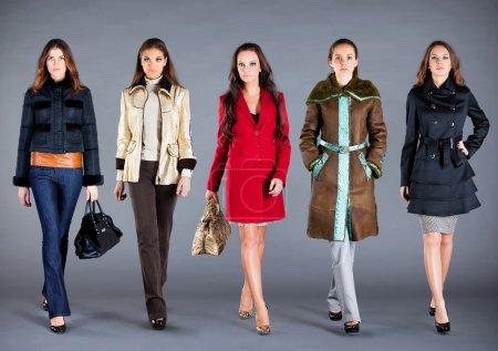 Photo pour Cinq filles dans différents vêtements, vêtements collection automne-hiver - image libre de droit