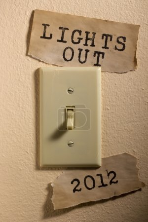 Photo pour Vieux papiers à côté d'un interrupteur d'éclairage qui disent 2012 et les lights out qui représente la fin du monde. - image libre de droit