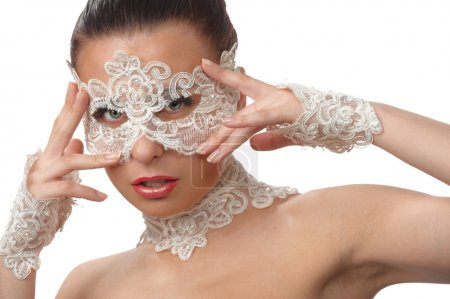 Beautiful woman with tender face in lace mask over her eyes