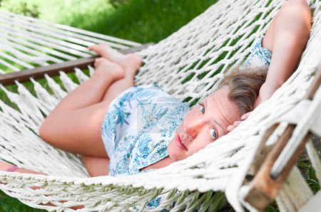 Photo for Sexy woman is lying in hammock and looking at camera - Royalty Free Image