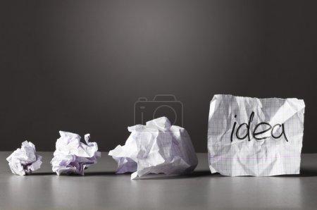 Photo pour Feuille de papier avec l'idée de mot et froissés bourres sur table. - image libre de droit
