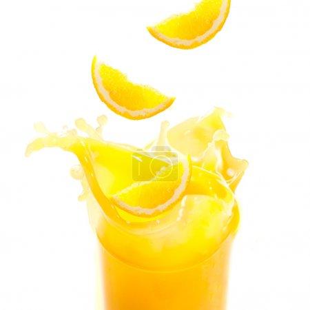 Photo pour Jus d'orange et les tranches sont éclaboussures en verre découper de fond blanc - image libre de droit