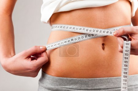 Photo for Sporty woman is measuring her waist on grey background - Royalty Free Image