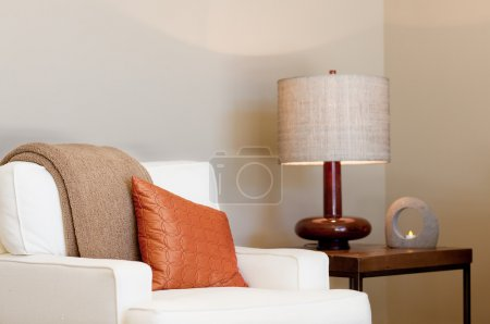 Photo for Cozy seat with throw and pillow, lamp and burning candle in the background - Royalty Free Image