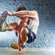 Young man sports exercises. On wall background....