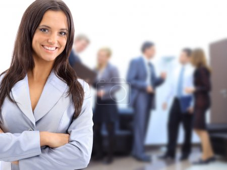 Photo for Successful business woman standing with her staff in background at office - Royalty Free Image