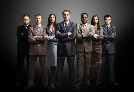 Photo for Business team formed of young businessmen standing over a dark background - Royalty Free Image