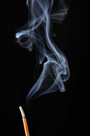 Photo pour Un bâton d'encens brûlant avec de la fumée sur fond noir - image libre de droit