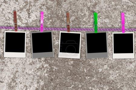 Photo pour Cinq photos vierges accrochées à une corde avec des pinces à linge sur un fond grunge - image libre de droit