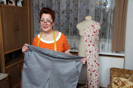 Photo pour Vieille femme coud des vêtements à la maison - image libre de droit