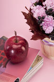 Still life with flower,magazines and apple