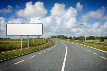 Photo pour Nouvelle autoroute avec marquage routier et panneau blanc par temps ensoleillé avec nuages - image libre de droit