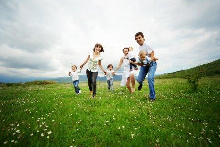 Foto de Grupo de padres felices con niños corriendo en campo - Imagen libre de derechos