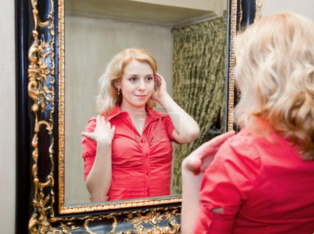 Reflection of young woman in a mirror