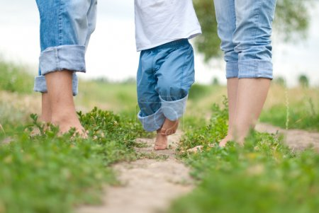 Photo for Feet from a baby and parents on the grass during a walk - Royalty Free Image