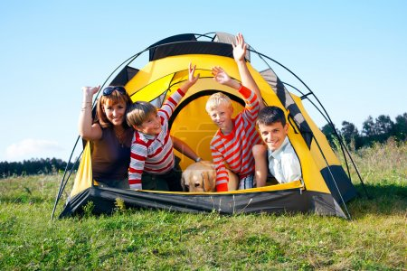 Photo for Happy family in the tent on sunny meadow - Royalty Free Image