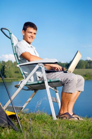 Photo pour Jeune homme avec ordinateur portable près de la tente - image libre de droit