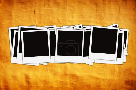 Photo for Stack of instant photos on vintage yellow wall with artistic shadows added - Royalty Free Image