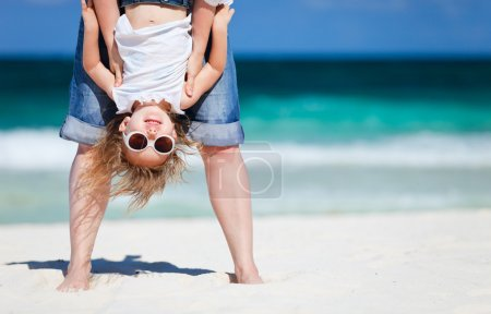 Photo for Mother holding her happy smiling daughter upside down having beach fun - Royalty Free Image