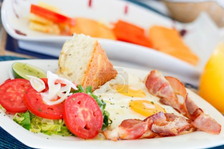 Photo for Delicious fried eggs with bacon and vegetables served for breakfast - Royalty Free Image