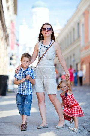 Photo for Young beautiful woman with her two kids in city at summer day - Royalty Free Image