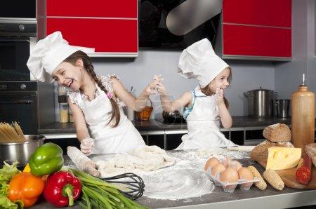 Photo pour Deux petites filles s'amusent sur la table de cuisine avec de la nourriture crue, des cuisiniers de vêtements - image libre de droit