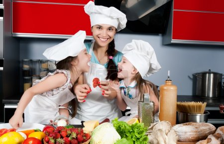 Photo for Mom teaches two daughters to cook at the kitchen table with raw food, clothing cooks - Royalty Free Image