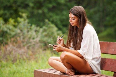 Photo pour Belle femme écrivant dans un petit livre - image libre de droit