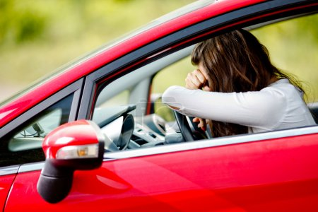 Young woman sitting depressed in car