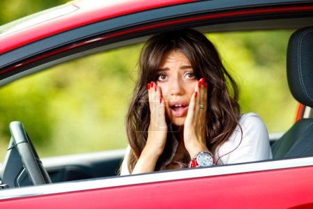 Photo for Young pretty scared woman in the car - Royalty Free Image
