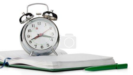 Photo for Alarm clock on notepad. Isolated on white background - Royalty Free Image
