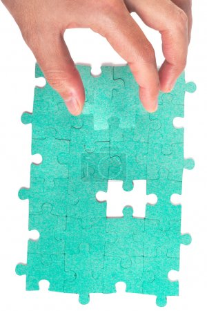 Hand inserting missing piece of green jigsaw puzzle into the hol