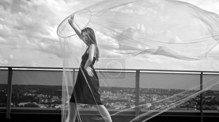 Photo for Romantic beauty with umbrella on a skyscraper roof. - Royalty Free Image