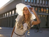 Portrait of a beautiful model in white retro hat. Street fashion photo.