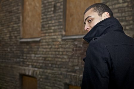 Young beautiful mulatto near old wold. Man and urban. Evening outdoor shoot
