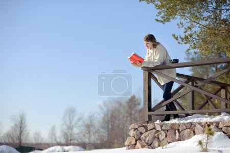 Photo for Girl reading the book on the street in the winter - Royalty Free Image