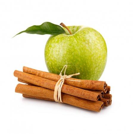reifer grüner Apfel mit Zimtstangen isoliert