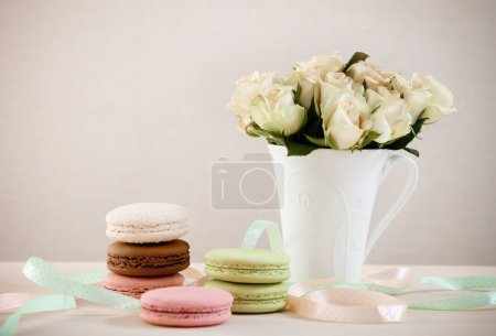 Photo for French macaroons on the table decorated with ribbons and roses - Royalty Free Image