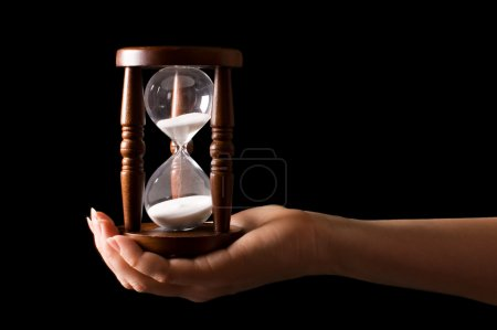 Photo for Hourglass in hands on a black background - Royalty Free Image