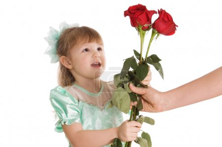 The little girl gives a bouquet of roses