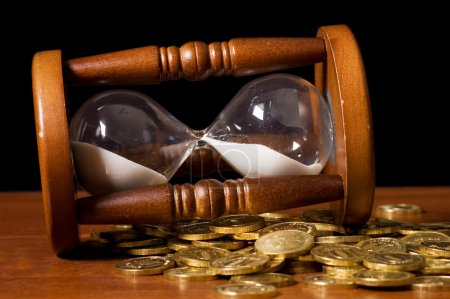 Hourglasses and coin On wooden table